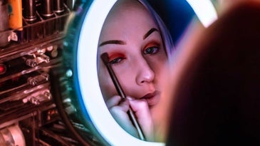 Woman putting on eyeshadow in vanity mirror with lights.