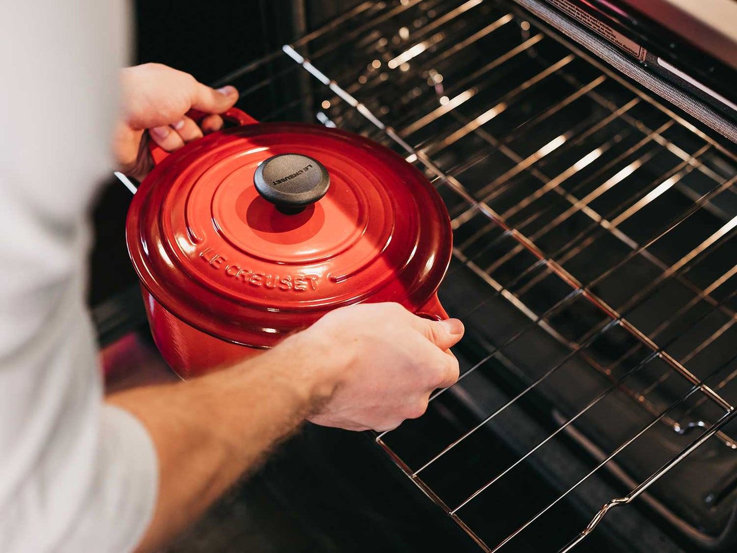 Man puts cast iron dutch oven into oven.