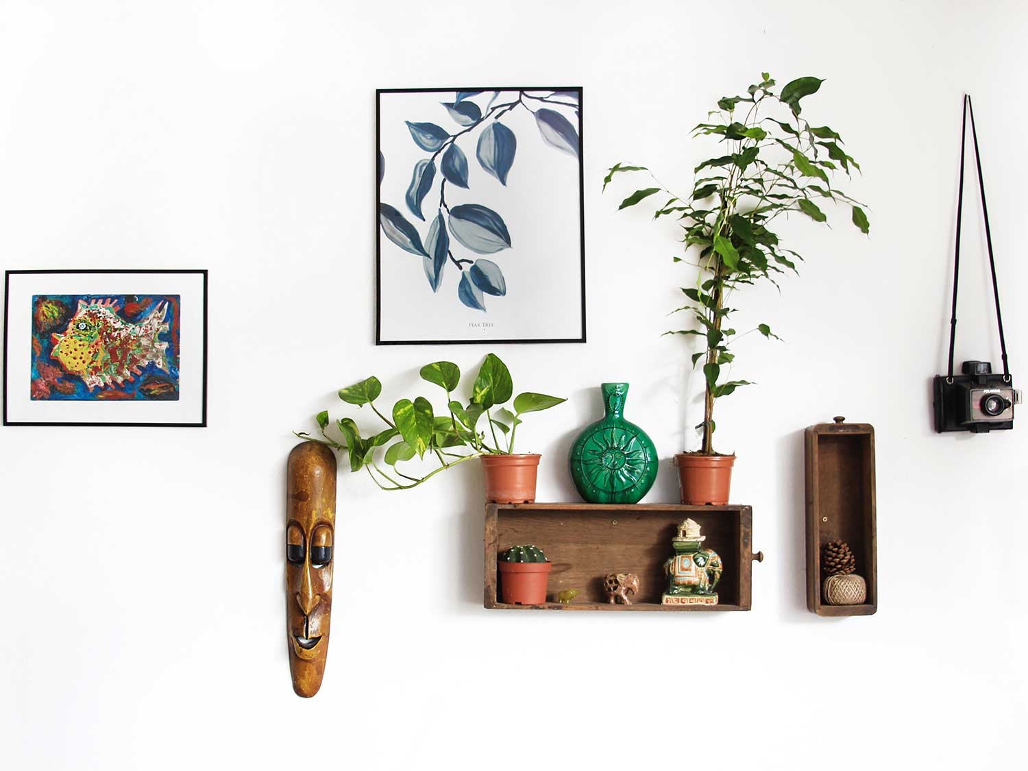 Frames hanging on wall with shelf and decorations.
