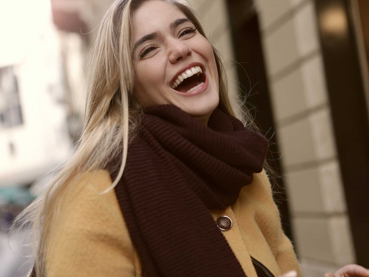 Woman with yellow jacket and black scarf smiling with all her teeth out.
