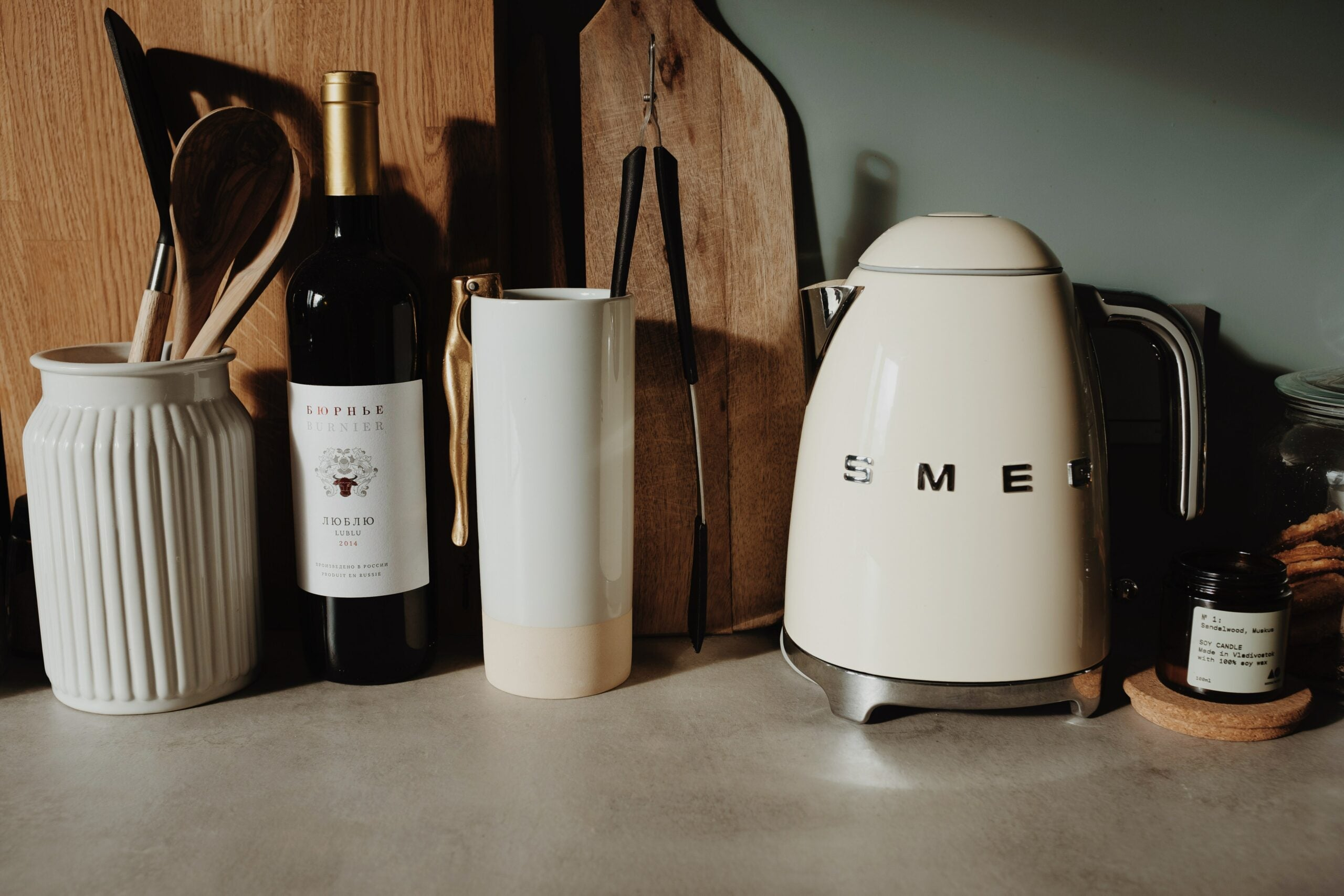 white electric kettle on a countertop with a bottle of wine and containers of kitchen tools