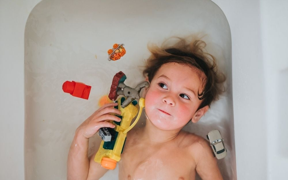 A kid playing with his toys while taking a bath
