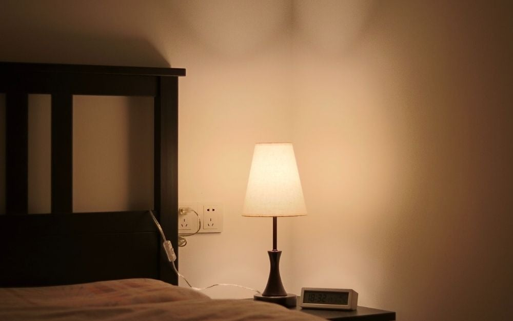 Lamp illuminating the bedroom standing on top of a bedside table.