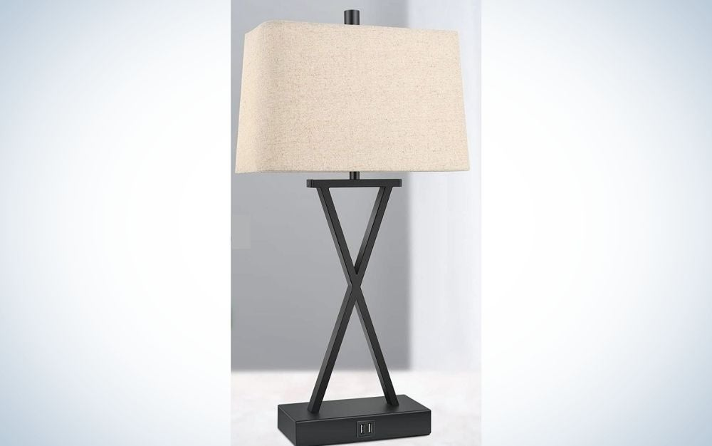 Cream colored lamp with crossed black tubes and black metallic lamp base.