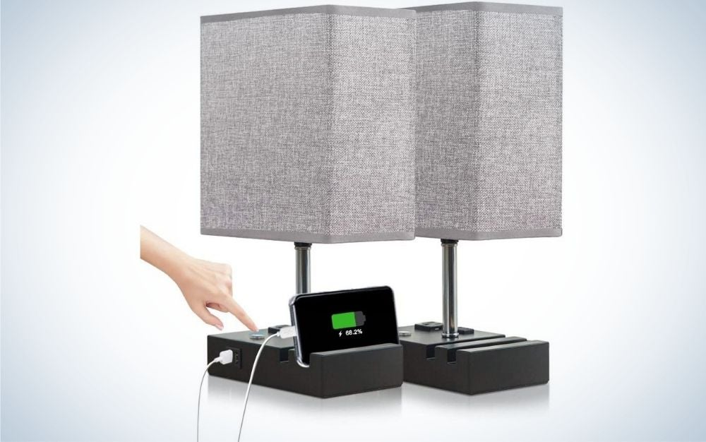 Human hand turning on a grey cuboid-like shaped lamp with black lamp base connected to a phone.