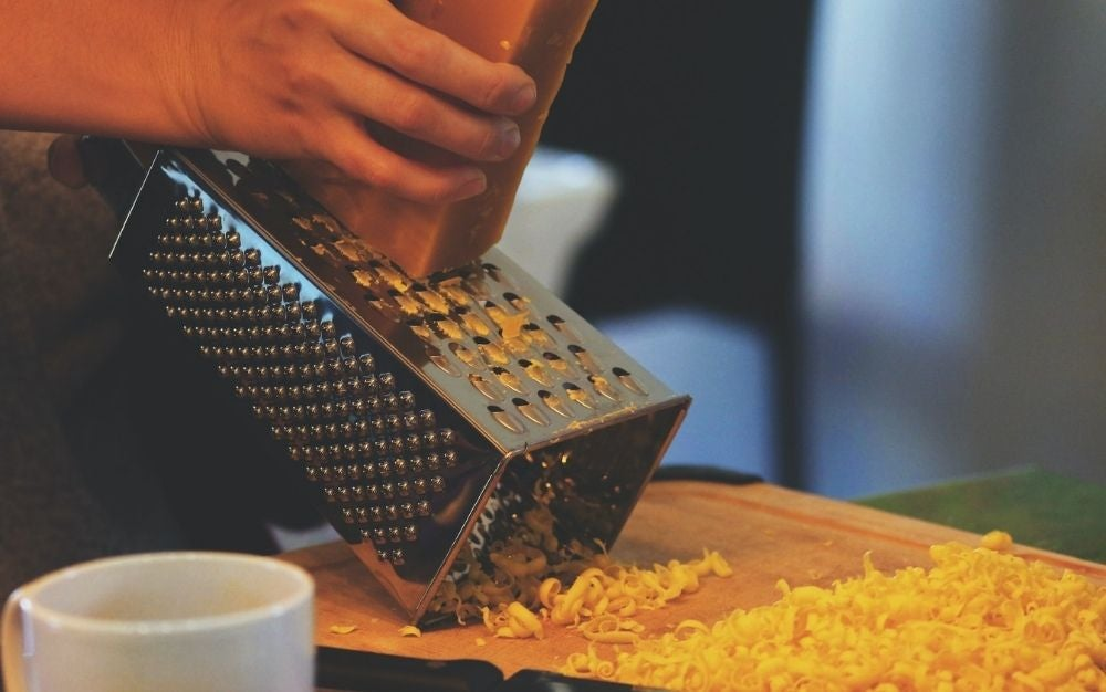 The hands of a man grinding cheese on the silver grater.
