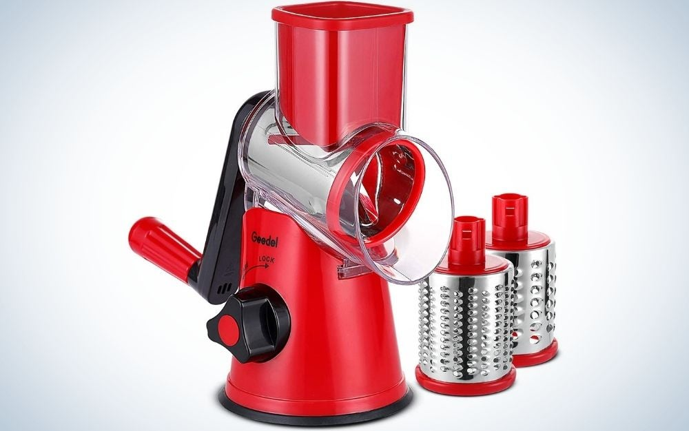 A red Geedel rotary cheese grater with three silver interchangeable blades.