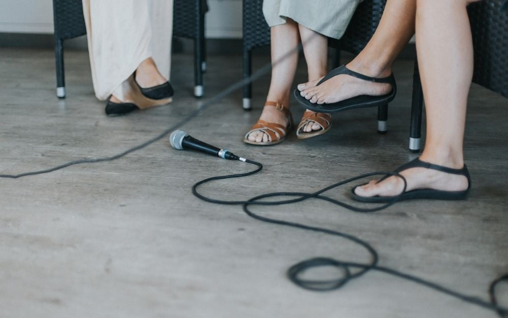 three women's legs with slippers and microphones around them.