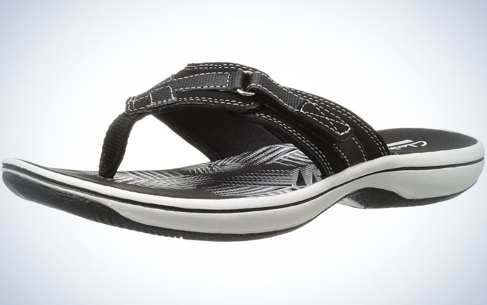 Black and white slippers with synthetic rubber sole picture form beside.