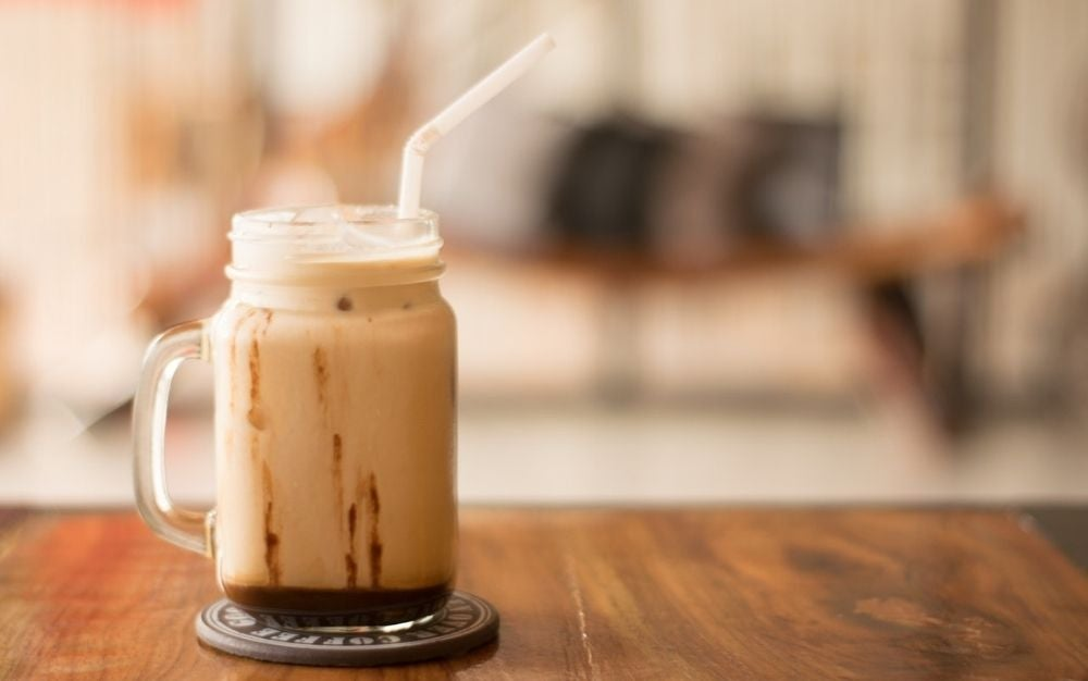 A large glass of cappuccino and a bend and plastic straw in it on a wooden table.