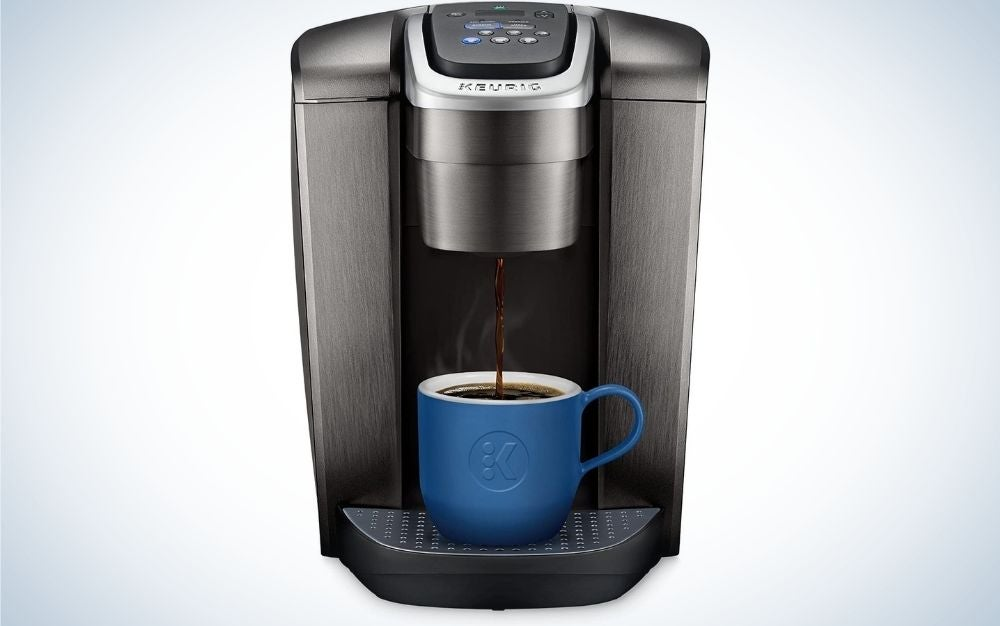 A dark grey coffee maker with a blue cup on it being filled with coffee.