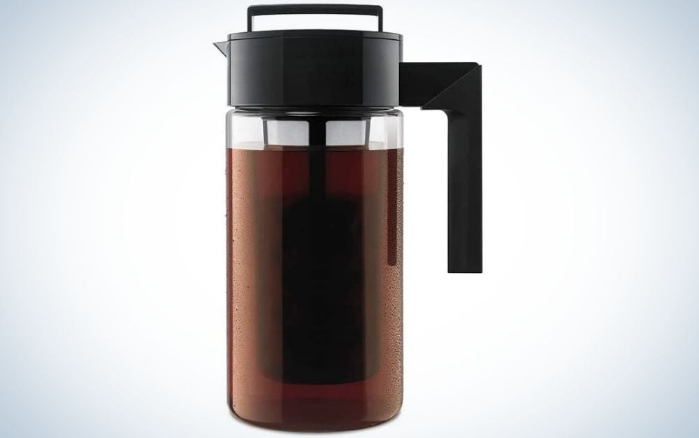 A glass pitcher filled with cherry color and with a black plastic silicone holder.