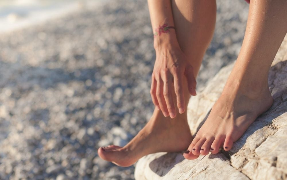 A woman's feet and hands standing on stones.