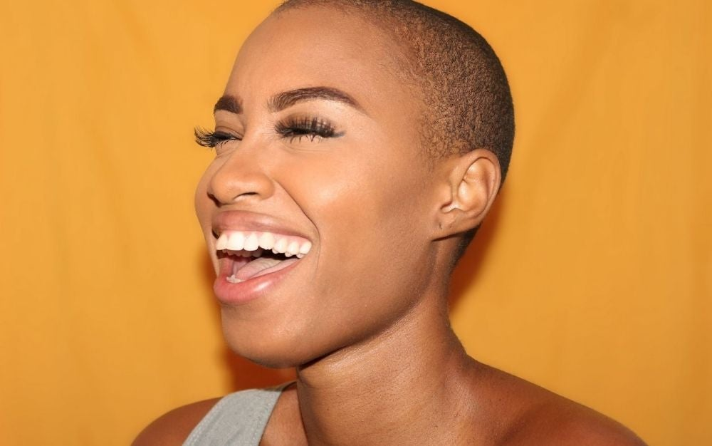 A woman laughing in a yellow background.