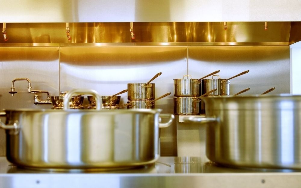 Some large aluminum pots and some upstairs in the kitchen gold color.