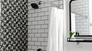 A bathroom with white tiles and black tiles, and a white plasma cover with a mirror on the side.