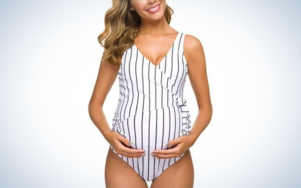 A pregnant woman with her hands on her belly wearing a bathing swim suit with white and black line into it.