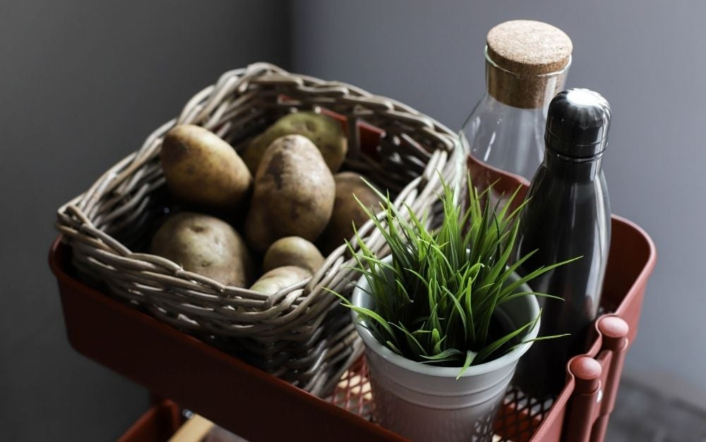 A basket of potato with two bottles beneath it and a small vase with green leaves into it.