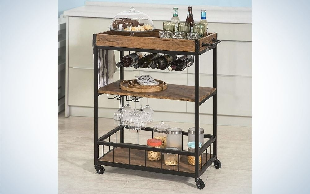 A kitchen serving cart with wheels and handle with three leveling feet and rustic brown and black with foods and wine glasses on it.