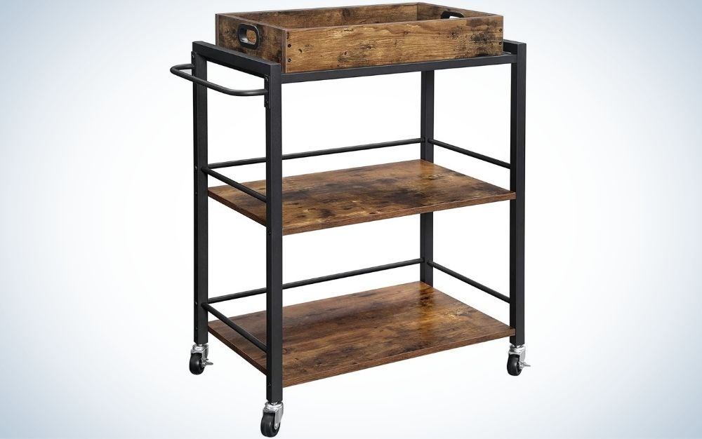 A kitchen serving cart with with wheels and handle with three leveling feet and rustic brown and black .