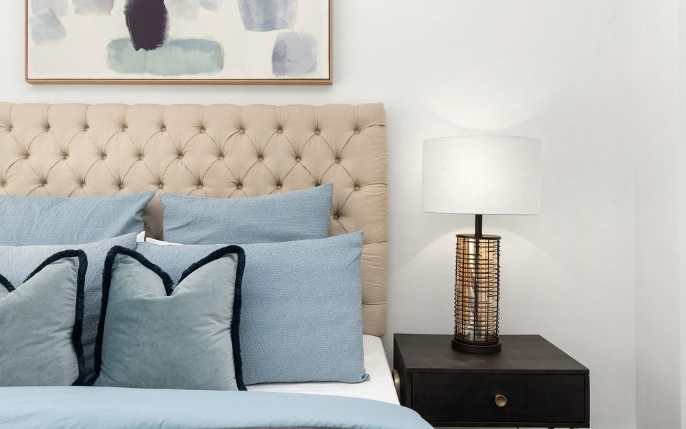 A bed with its beige head and light blue pillows and next to it a lamp with its gold and white body at the top of the pot.