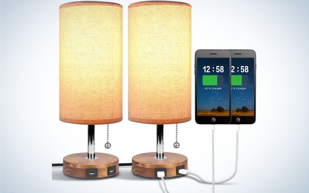 Dual gold bedside table lamp in a cylindrical form and golden color with a wooden seal with two parts of USB charger and two phones with charging screens.