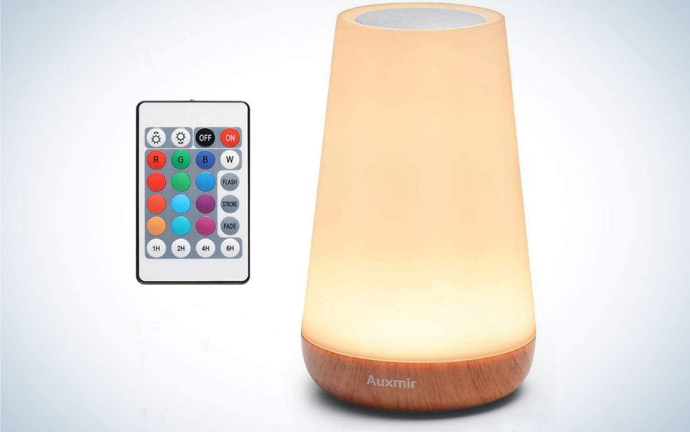 A rose colored lamp in a cylindrical shape and with wooden support as well as a remote control with different colors and numbers in it.