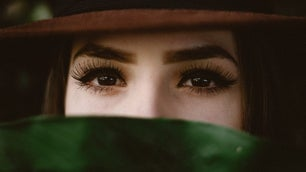 A woman eyes focused on camera with a brown hat and green scarf.