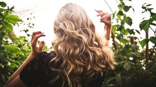 A blonde hair girl with a curly and wave hair style from behind between green flowers.