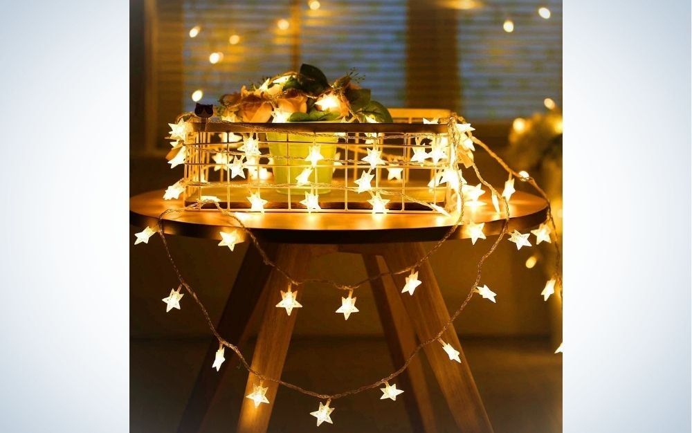 A wooden table above it is a basket of gold-colored lights scattered on the table and below it.