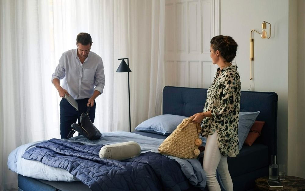 A couple standing on either side of a double bed as they adjust and arrange the blue bedspreads and pillows on the bed.