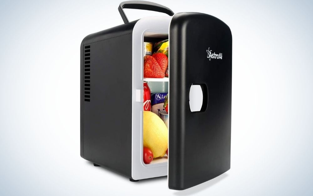 A small refrigerator with a holder on top of it and all in black with the brand name on its door, as well as open and full of fruit and food in it.