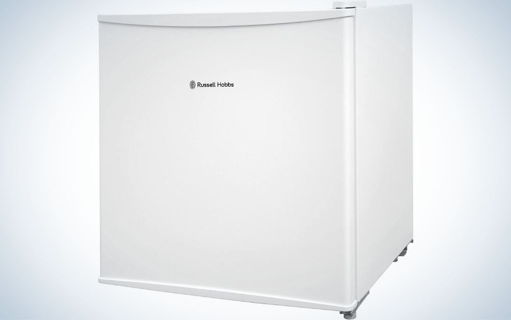 A small white refrigerator in the shape of a square with the brand name on it.