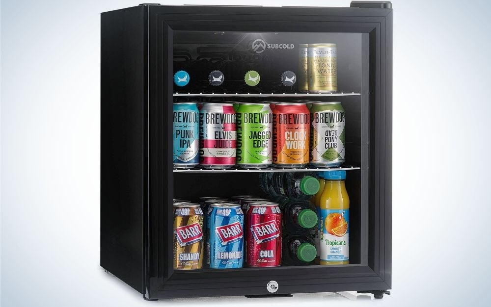 A black and square refrigerator with a transparent glass in front which is filled with various drinks inside.