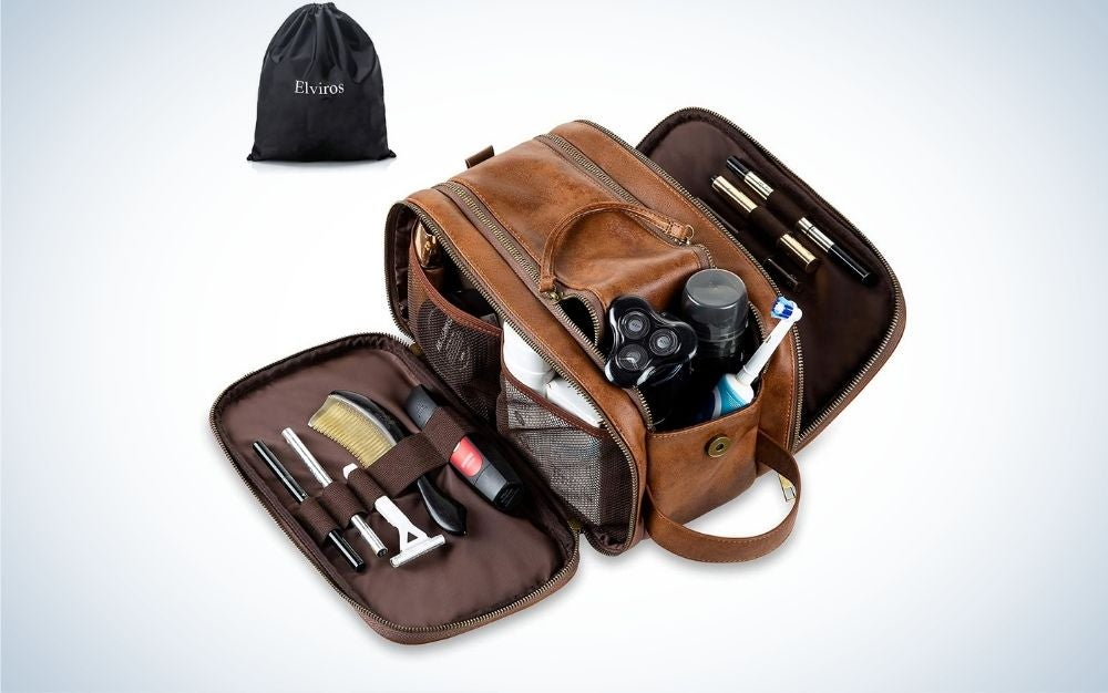 A small brown leather bag with two open and stuffed side pockets and various personal products of a man arranged inside it.