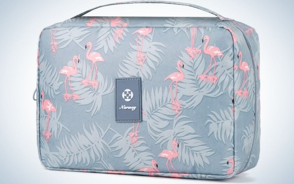 A bag with blue coral color and small flowers in pink, with the brand name in the middle and with a square shape with a light gray chain.