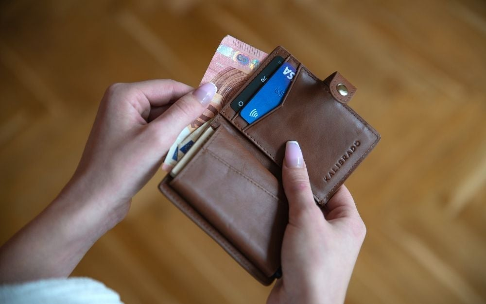 The hands of a woman holding a light brown wallet as she pulls out the money in it.