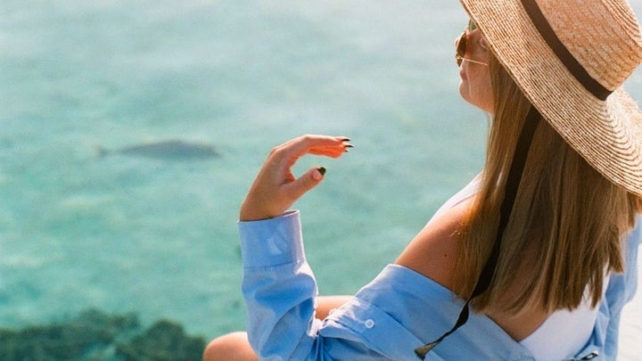 A woman in a blue skirt and beige hat in front of the sea and then sun.