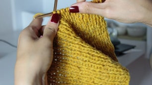 Hands of a woman who are making slippers with a thick yellow thread with two knitting needles.