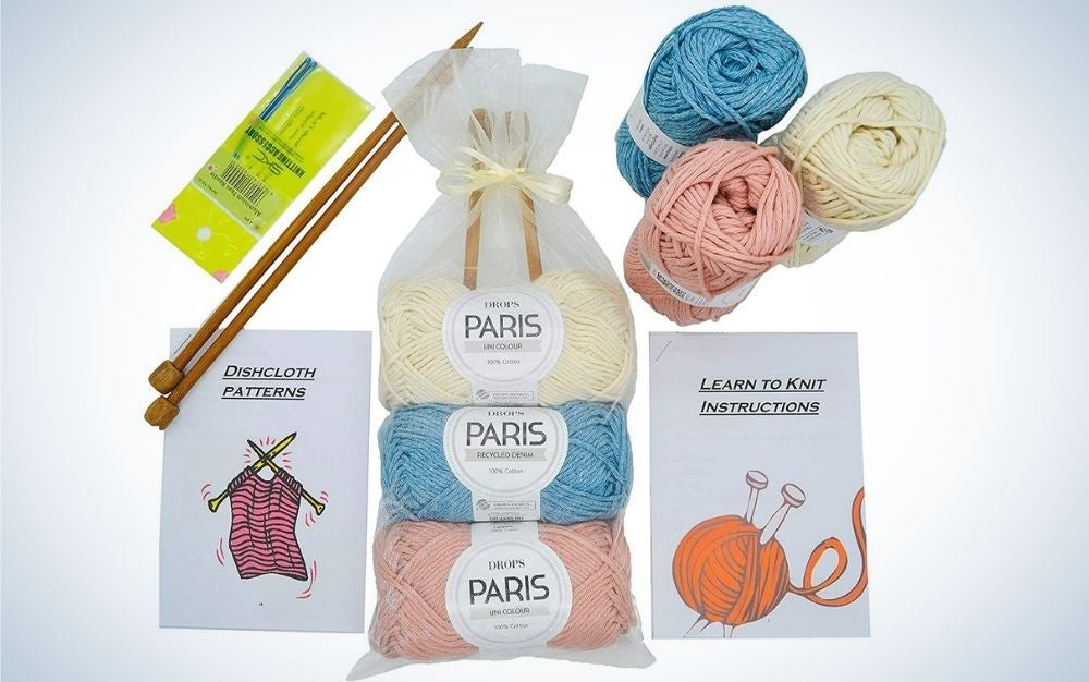 Some knitting kits in the shape of a ball and different colors, as well as some gold colored needles in them.