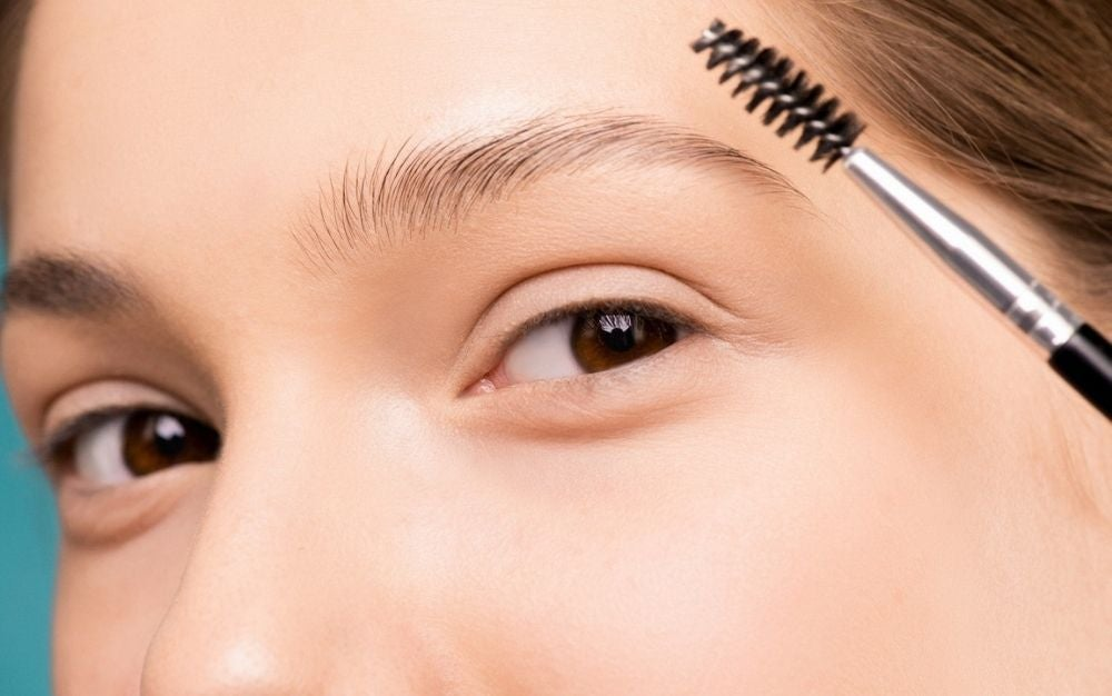 A girl as she poses with her clean face and a brow brush near her eyes and eyebrows.