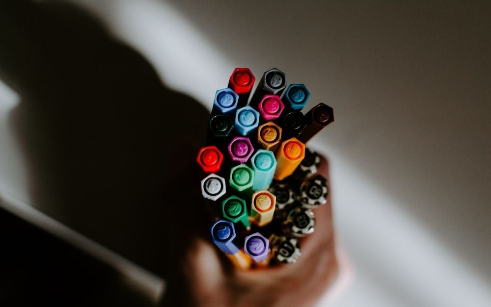 A brunch full hand with colorful whiteboard pens.