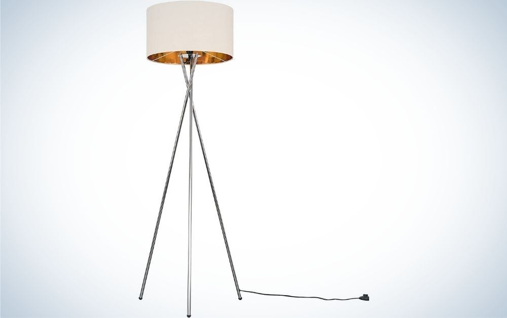 Modern polished chrome metal tripod standing lamp for living room with a beige and gold cylinder shade